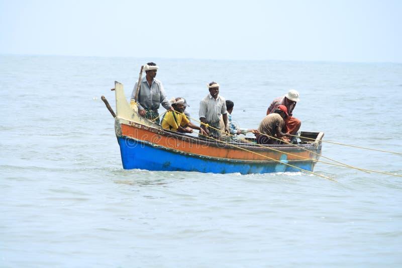 Los pescadores hacen la pesca usando el barco y la red de pesca imágenes de archivo libres de regalías