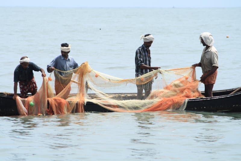 Los pescadores hacen la pesca usando el barco y la red de pesca foto de archivo libre de regalías