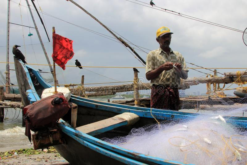 Los pescadores limpian sus redes de pesca contra el contexto de estructuras pesqueras chinas masivas imagenes de archivo