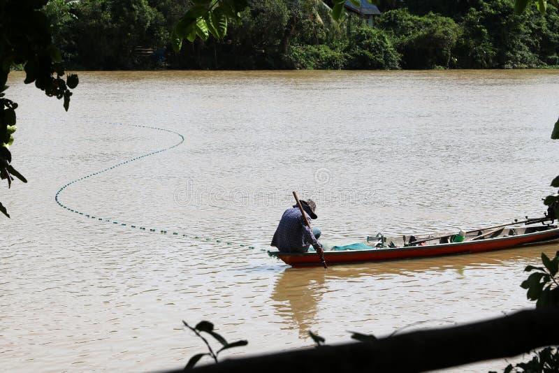 Los pescadores locales en el barco de madera con una malla o las trampas pescan a lo largo de t imágenes de archivo libres de regalías