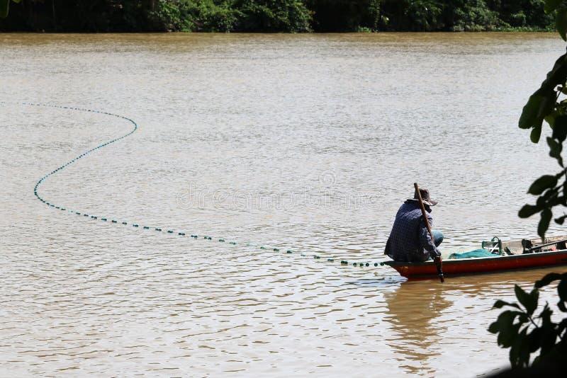 Los pescadores locales en el barco de madera con una malla o las trampas pescan a lo largo de t fotos de archivo libres de regalías