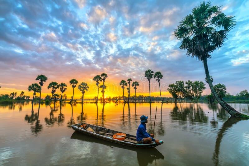 Los pescadores no identificados se sientan en un barco que miran el amanecer que saludan el nuevo día foto de archivo