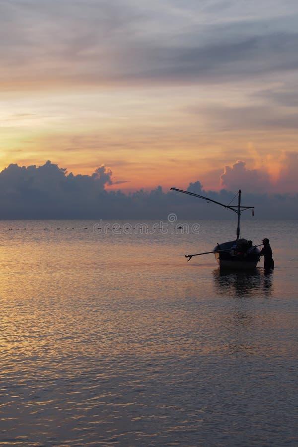 Los pescadores que preparan el barco para salir pescar por la mañana fotos de archivo