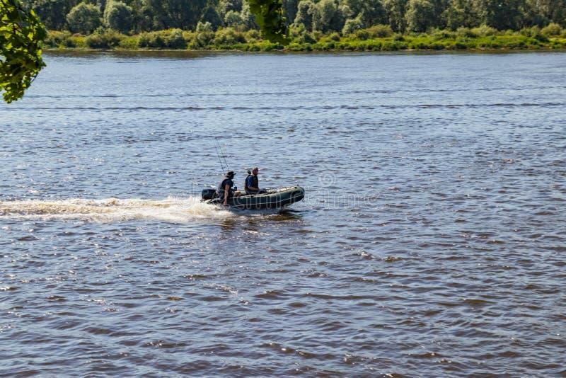 Los pescadores van motora en un río que busca pescados en un día de verano soleado imagenes de archivo
