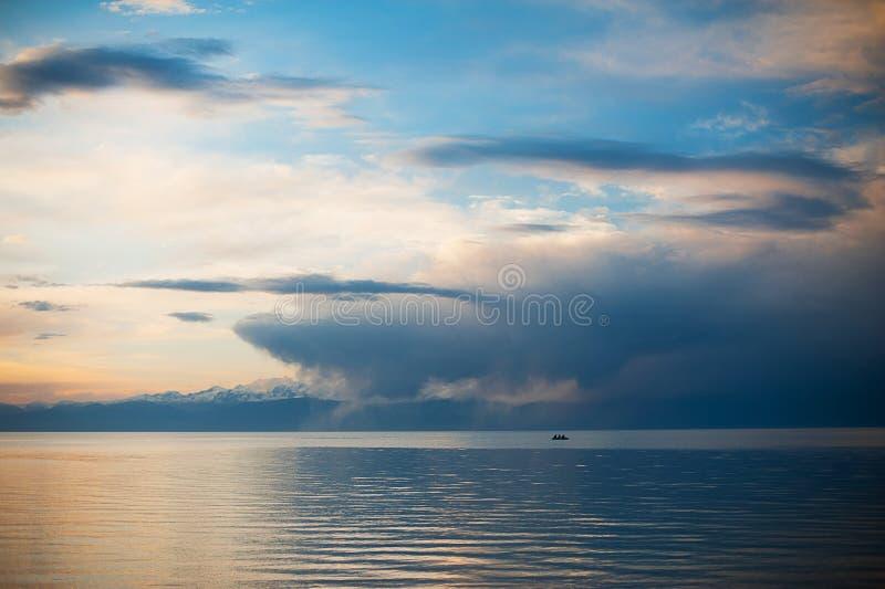 Los pescadores van a pescar de un barco en la salida del sol Puesta del sol en el lago, barco Hombre de Blissed exultado bajo vis foto de archivo libre de regalías