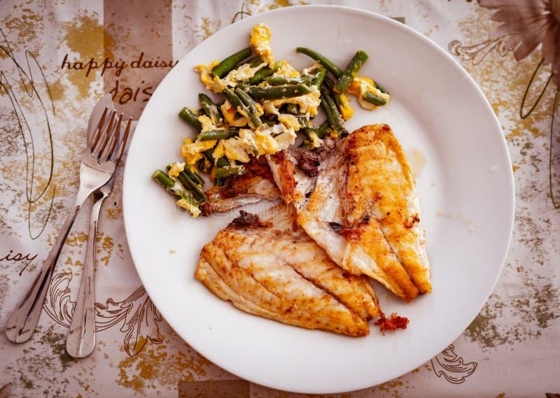 Los pescados asados a la parrilla cortan y los huevos revueltos y las verduras en la placa, visión superior imágenes de archivo libres de regalías