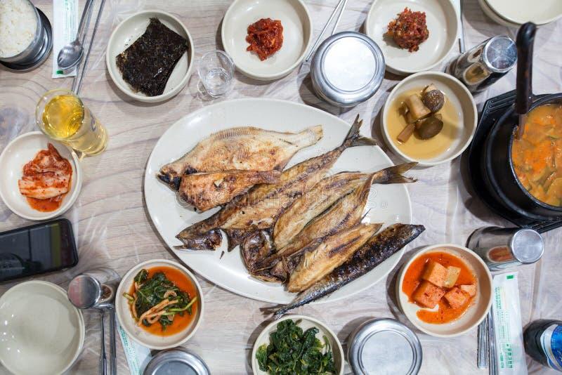 Los pescados asados a la parrilla sirvieron en el plato blanco durante tiempo de cena fotos de archivo