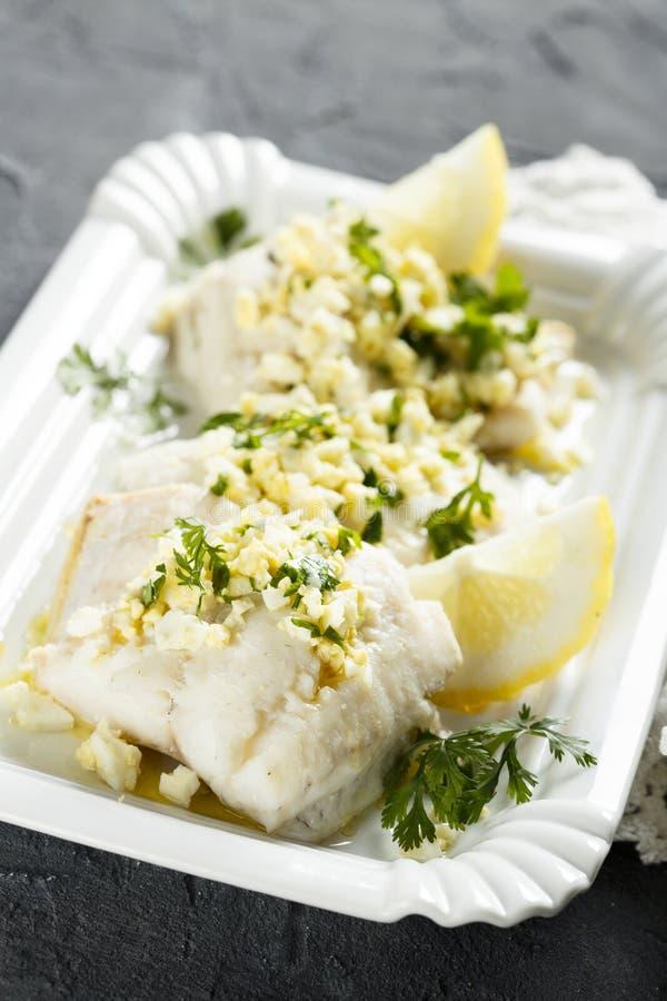 Los pescados blancos cocinaron con la salsa del perejil y del limón fotografía de archivo