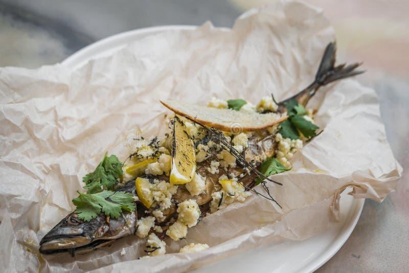 Los pescados cocieron en el pergamino con queso, las hierbas y el limón imagen de archivo