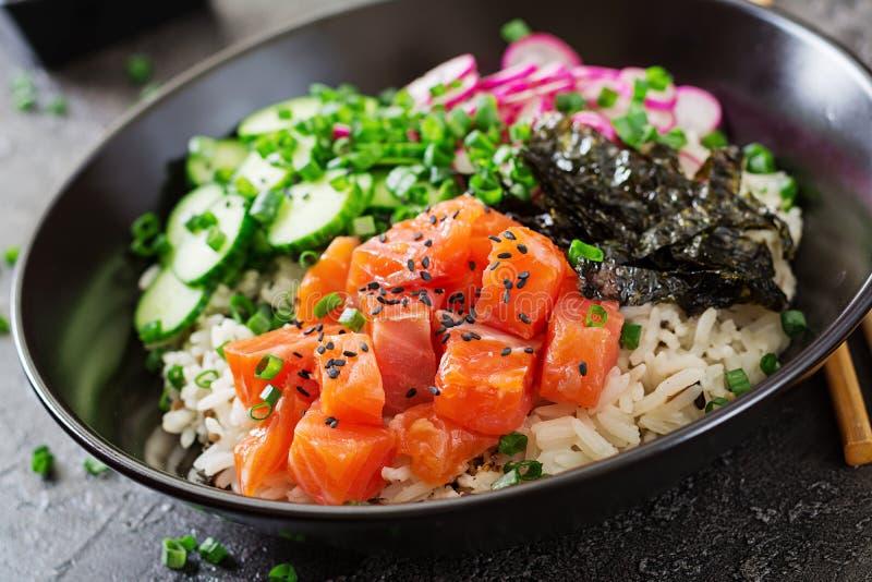 Los pescados de color salmón hawaianos empujan el cuenco con arroz, el rábano, el pepino, el tomate, las semillas de sésamo y las fotografía de archivo libre de regalías