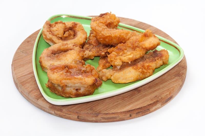Los pescados fritos sirvieron en una placa triangular verde imagen de archivo libre de regalías