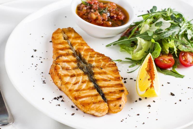 Los pescados rojos grandes del filete de color salmón en la parrilla con el limón, salsa y imagenes de archivo