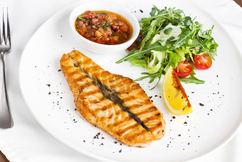 Los pescados rojos grandes del filete de color salmón en la parrilla con el limón, la salsa y las verduras foto de archivo libre de regalías