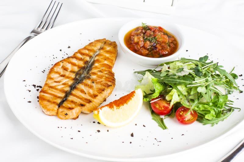 Los pescados rojos grandes del filete de color salmón en la parrilla con el limón, la salsa y las verduras fotos de archivo libres de regalías