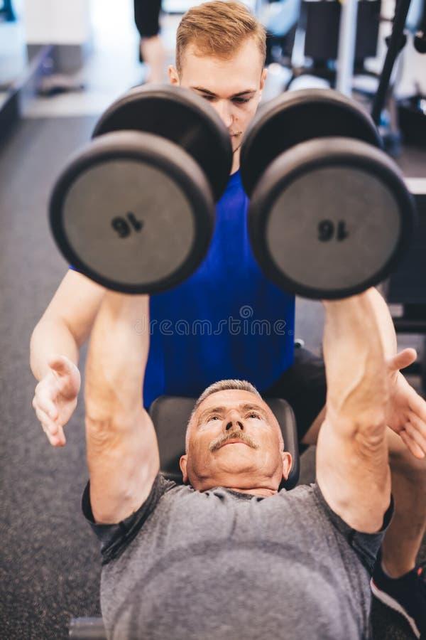 Los pesos de elevación del hombre mayor ayudaron por el instructor de gimnasio fotos de archivo