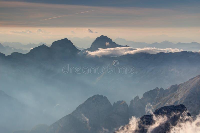 Los picos agudos de Jalovec y de Mangart se elevan sobre el valle nebuloso de Trenta fotografía de archivo