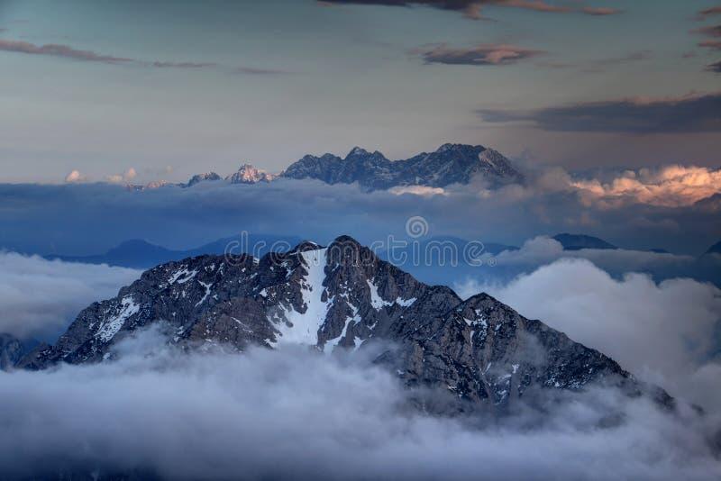 Los picos de la gama de Karavanke y las montañas de Kamnik-Savinja suben sobre las nubes imagenes de archivo