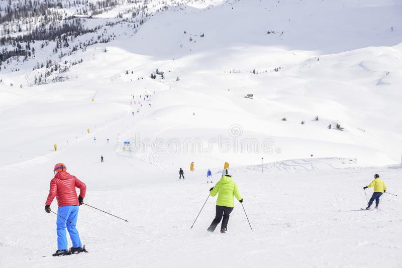 Los picos de las montañas de las montañas cubiertas con nieve las cuestas del esquí apretaron con los esquiadores en un día de in fotos de archivo