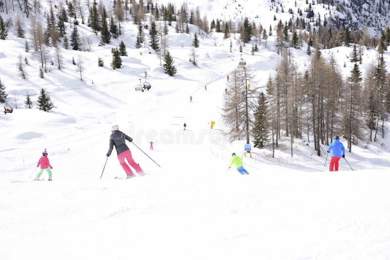 Los picos de las montañas de las montañas cubiertas con nieve las cuestas del esquí apretaron con los esquiadores en un día de in imagenes de archivo