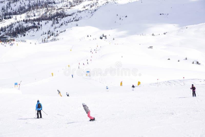 Los picos de las montañas de las montañas cubiertas con nieve las cuestas del esquí apretaron con los esquiadores en un día de in imágenes de archivo libres de regalías
