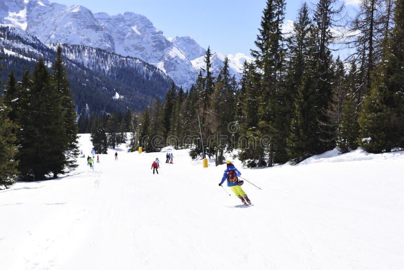 Los picos de las montañas de las montañas cubiertas con nieve las cuestas del esquí apretaron con los esquiadores en un día de in foto de archivo libre de regalías