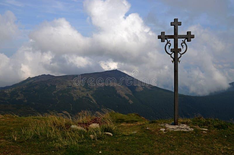 Los picos de las monta?as c?rpatas Cordilleras cubiertas con los bosques debajo de las nubes azules foto de archivo