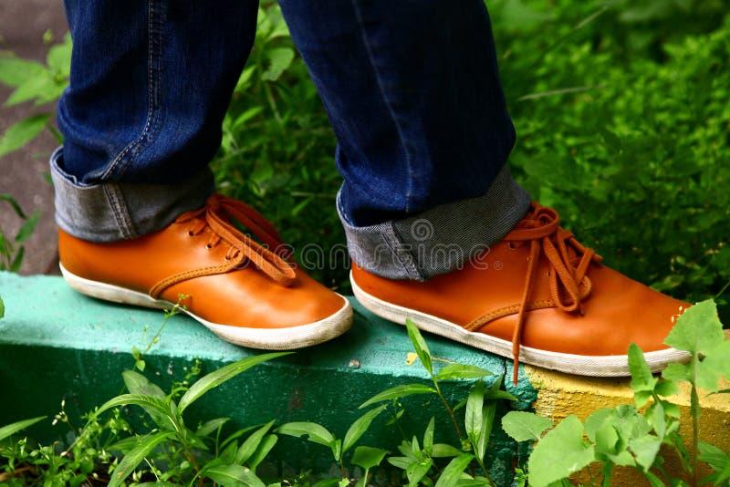 Los pies con los zapatos cómodos anaranjados caminan en la frontera en la calle de la ciudad imagen de archivo libre de regalías