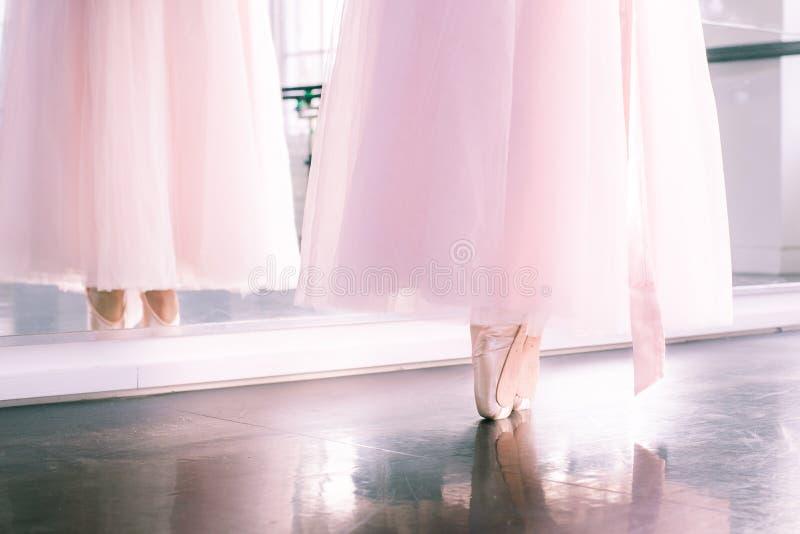 Los pies de Ballerine en zapatos del pointe y tutú airoso rosado bordean el reflecte fotos de archivo libres de regalías