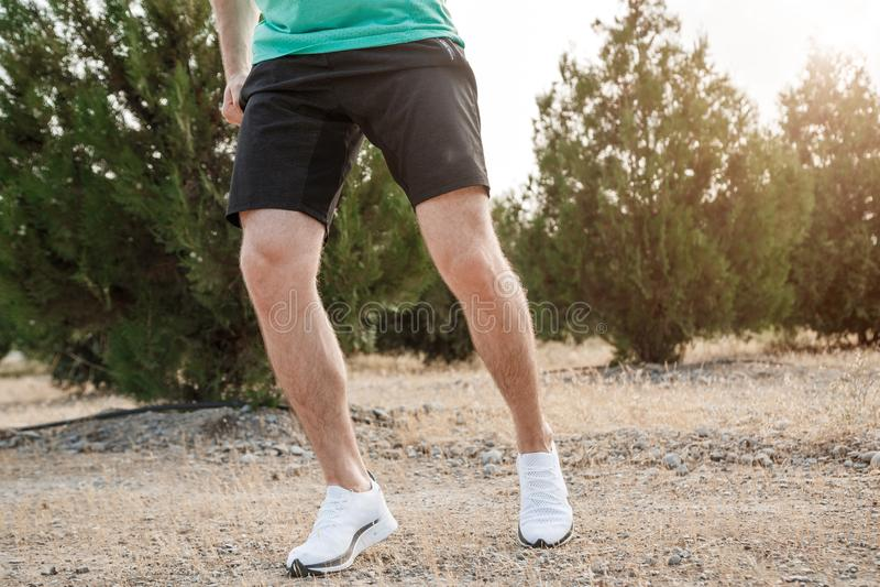 Los pies de los hombres en las zapatillas de deporte blancas que corren sobre terreno áspero Campo a través que corre con el foco foto de archivo