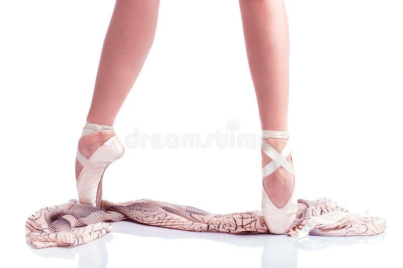 Los pies de la bailarina en pointe y con la bufanda de seda en el fondo blanco fotos de archivo