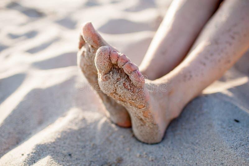 Los pies de la muchacha en la arena fotografía de archivo