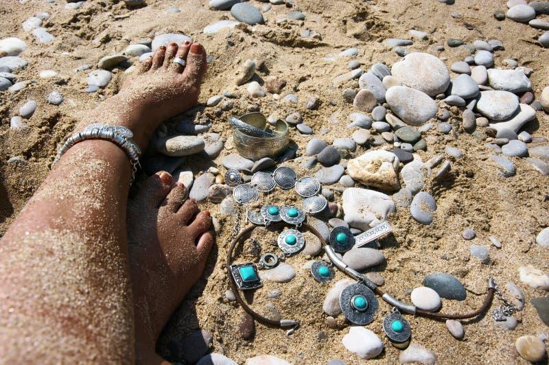 Los pies de la mujer con boho diseñan la joyería en la playa fotografía de archivo