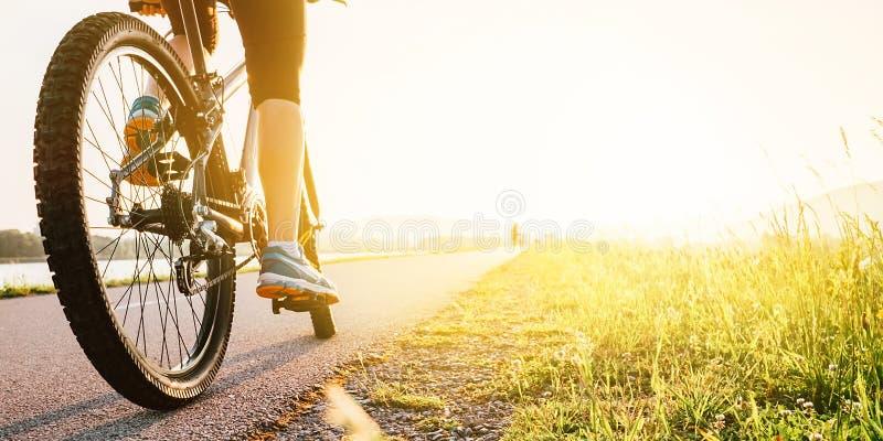 Los pies de la mujer en bycikle pedal en luz de la puesta del sol imagen de archivo