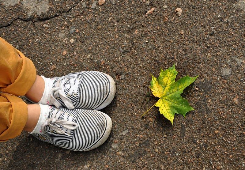 Los pies de la mujer en zapatillas de deporte en el asfalto fotos de archivo libres de regalías