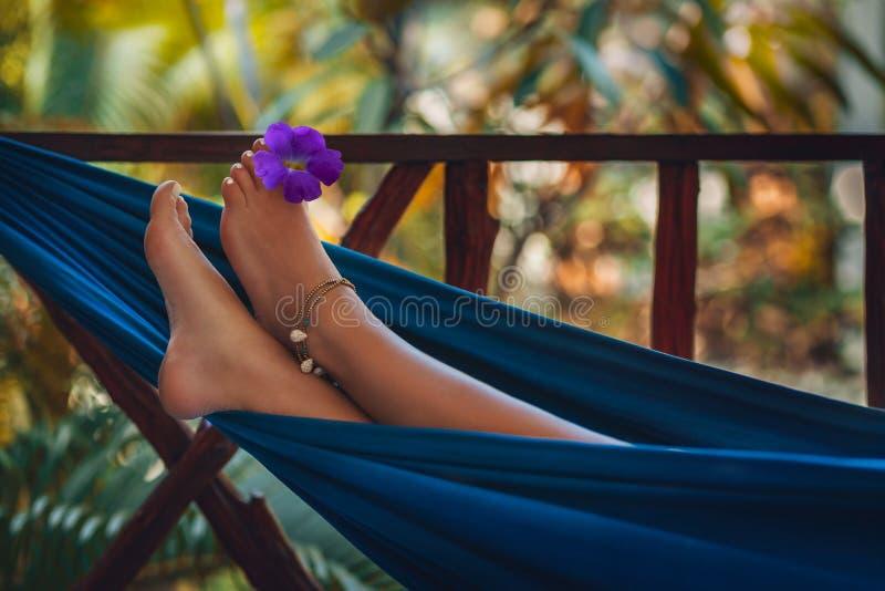 Los pies de la mujer se cierran encima de la mentira en hamaca foto de archivo libre de regalías