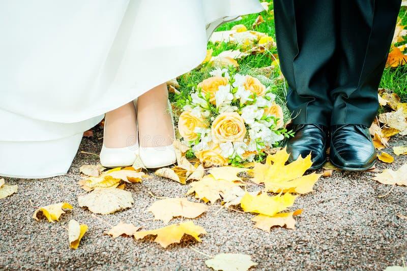 Los pies de la novia y del novio en otoño parquean fotos de archivo