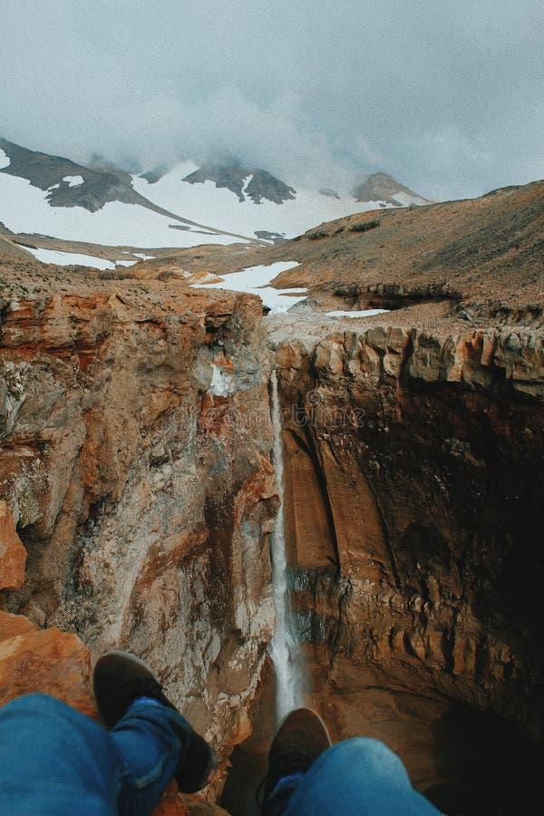 Los pies de la persona al borde de la roca cerca de una cascada fina hermosa y de colinas nevosas en fondo fotos de archivo