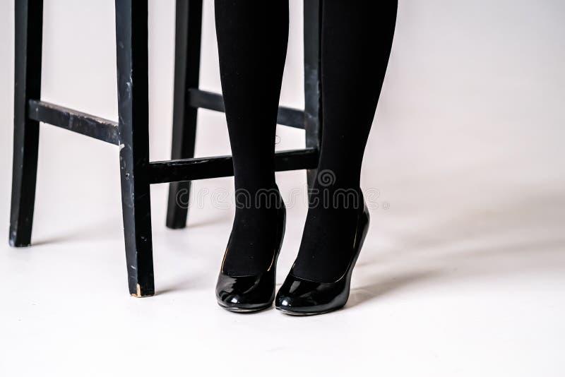 Los pies de las mujeres en medias o medias negras fotografía de archivo