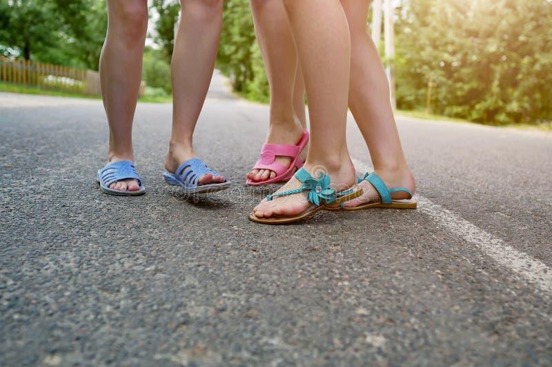 Los pies de los niños en deslizadores en el asfalto foto de archivo