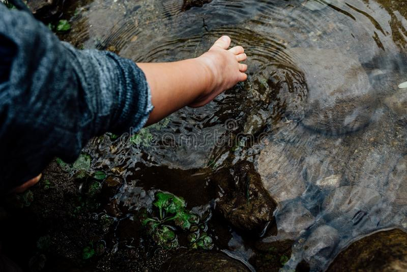 Los pies de los niños están tocando el agua que crea ondulaciones Muestra de la esperanza y de la niñez de la felicidad Muchacho  foto de archivo libre de regalías