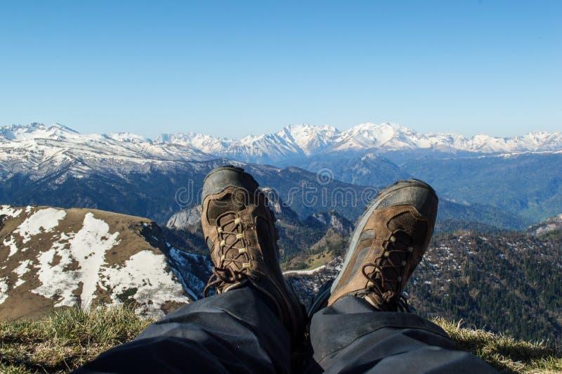 Los pies de un hombre en botas contra la perspectiva de coronado de nieve imagen de archivo libre de regalías