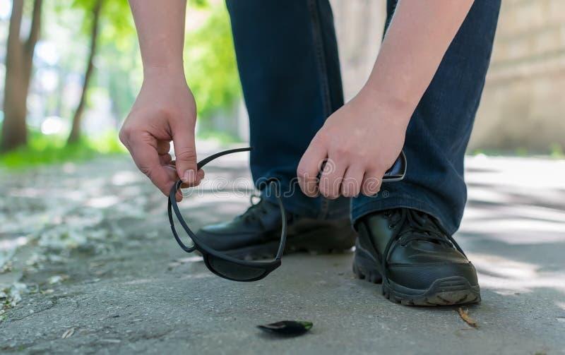 Los pies del hombre en una calle de la ciudad que se coloca en un camino peatonal del asfalto y aumenta las gafas de sol caidas y fotografía de archivo