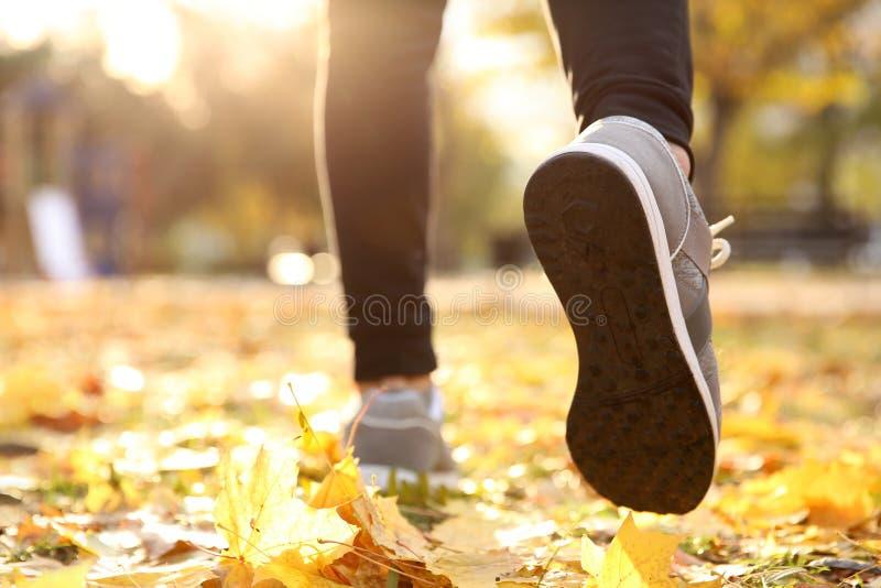 Los pies del hombre joven que corren en otoño parquean fotografía de archivo