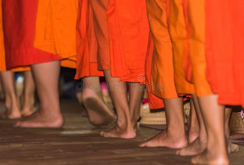 Los pies del primer de los monjes Alimentación de los monjes El ritual se llama Tak Bat, Luang Prabang, Laos imágenes de archivo libres de regalías