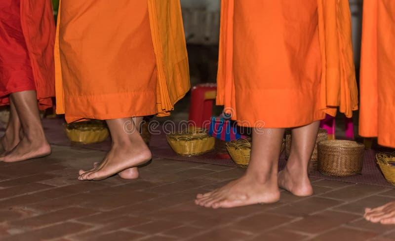 Los pies del primer de los monjes Alimentación de los monjes El ritual se llama Tak Bat, Luang Prabang, Laos foto de archivo