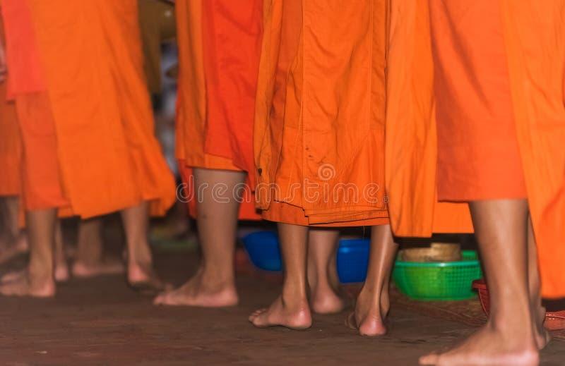 Los pies del primer de los monjes Alimentación de los monjes El ritual se llama Tak Bat, Luang Prabang, Laos foto de archivo libre de regalías