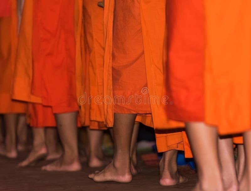 Los pies del primer de los monjes Alimentación de los monjes El ritual se llama Tak Bat, Luang Prabang, Laos imagen de archivo libre de regalías