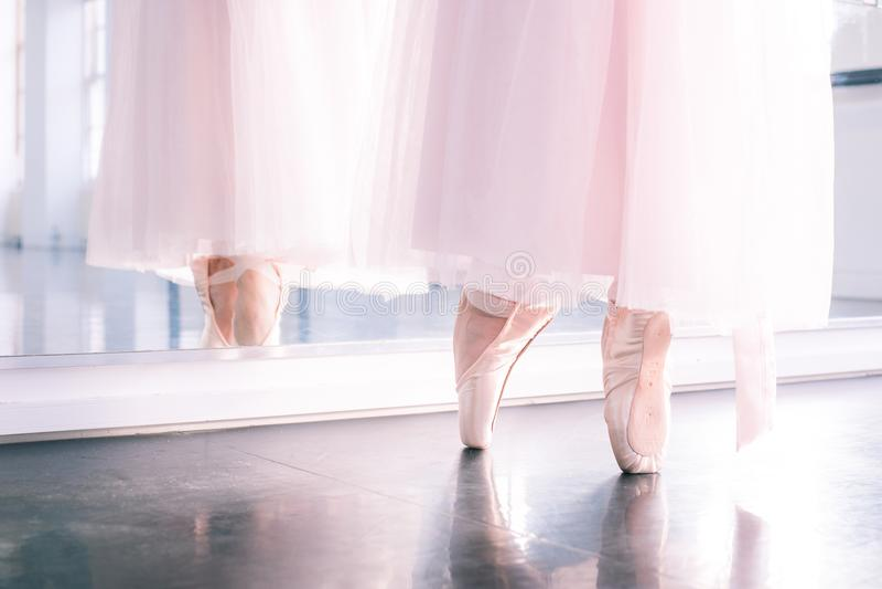 Los pies del ` s de la bailarina en zapatos del pointe y tutú airoso rosado bordean el reflecte fotos de archivo libres de regalías