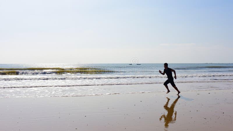 Los pies desnudos sirven el funcionamiento en la playa con las ondas fotos de archivo