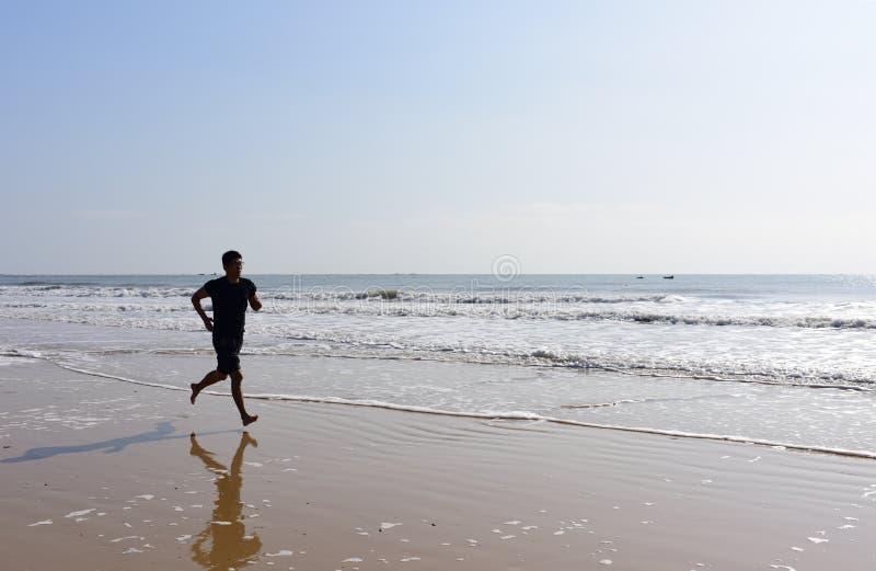 Los pies desnudos sirven el funcionamiento en la playa con las ondas imágenes de archivo libres de regalías